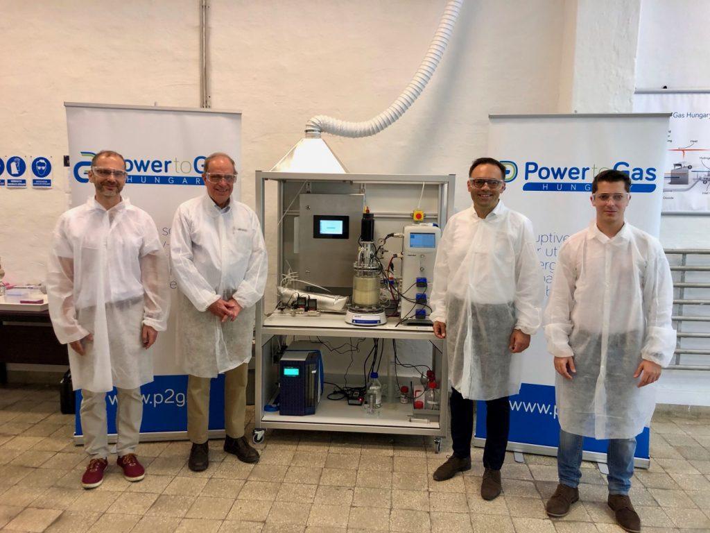 A Power-to-Gas Hungary Kft által fejlesztett biometanizációs prototípus a startup oroszlányi laboratóriumában.  Balról jobbra: Dr. Sinóros-Szabó Botond műszaki igazgató, Dr. Laurens J. Mets professzor, a power-to-gas technológia szabadalmaztatója, Dr. Csedő Zoltán ügyvezető igazgató, Zavarkó Máté üzletfejlesztési igazgató.
