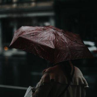 nő esernyővel sétál a városban