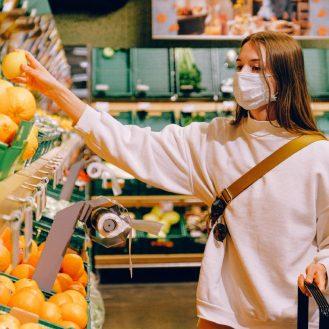 lány leemel a boltban a polcról egy citromot